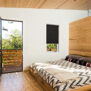 Modern inredning av ett mellanstort huvudsovrum, med vita väggar, plywoodgolv och brunt golv