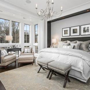 Пример оригинального дизайна: большая хозяйская спальня в классическом стиле с бежевыми стенами, темным паркетным полом, стандартным камином и фасадом камина из камня