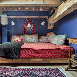 Foto de dormitorio de estilo zen, de tamaño medio, sin chimenea, con paredes azules, suelo de madera clara y suelo marrón