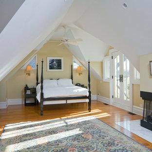 Foto de dormitorio tipo loft, tradicional renovado, de tamaño medio, con paredes beige, suelo de madera en tonos medios, chimenea de esquina y marco de chimenea de baldosas y/o azulejos