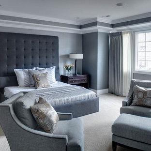 シカゴの巨大なトランジショナルスタイルのおしゃれな主寝室 (カーペット敷き、石材の暖炉まわり、グレーの壁) のインテリア