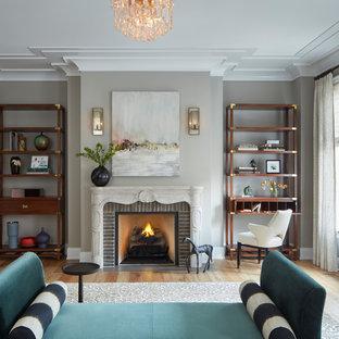 Diseño de dormitorio principal, tradicional, extra grande, con paredes grises, suelo de madera clara, chimenea tradicional y marco de chimenea de ladrillo