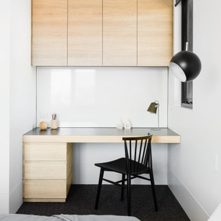 This is an example of a contemporary bedroom in Sydney with white walls and black floor.