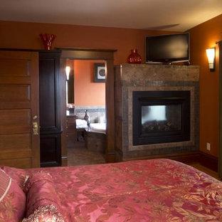 Ejemplo de dormitorio principal, de estilo americano, grande, con parades naranjas, suelo de madera clara, chimenea de doble cara y marco de chimenea de baldosas y/o azulejos