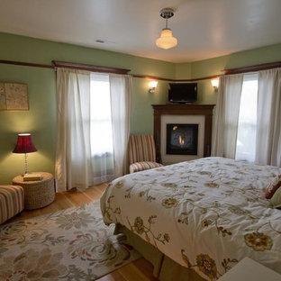 Modelo de dormitorio principal, de estilo americano, grande, con paredes verdes, suelo de madera clara, chimenea de esquina y marco de chimenea de madera