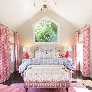 Cette image montre une grand chambre parentale traditionnelle avec un mur beige et un sol en bois foncé.