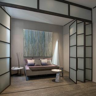 Imagen de dormitorio tipo loft, moderno, de tamaño medio, con paredes grises y suelo de madera en tonos medios