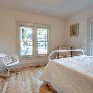 Idéer för att renovera ett litet amerikanskt sovrum, med vita väggar och ljust trägolv