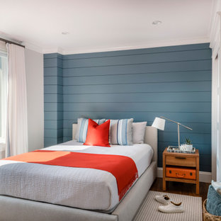 Beach style bedroom in Boston with blue walls, dark hardwood floors, brown floor and planked wall panelling.