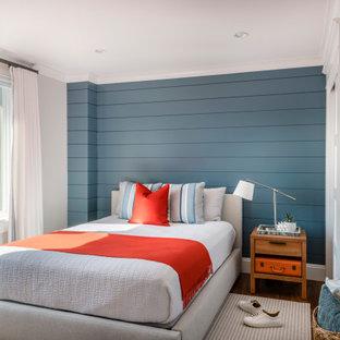 Maritimes Schlafzimmer mit blauer Wandfarbe, dunklem Holzboden, braunem Boden und Holzdielenwänden in Boston