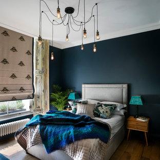 Cette photo montre une chambre parentale éclectique avec un mur bleu et un sol en bois foncé.