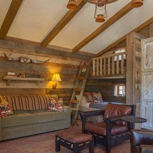 На фото: большая гостевая спальня с коричневыми стенами, кирпичным полом и красным полом без камина с
