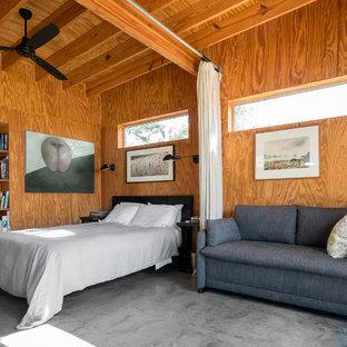 Ispirazione per una camera da letto industriale con pavimento in cemento