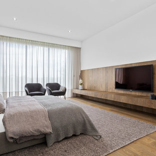 Design ideas for a contemporary bedroom in Perth with white walls, medium hardwood floors and brown floor.