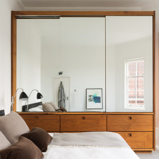 Example of a mid-sized danish master bedroom design in London with white walls