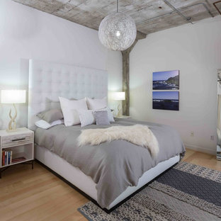 Design ideas for an industrial loft-style bedroom in San Francisco with white walls and light hardwood floors.
