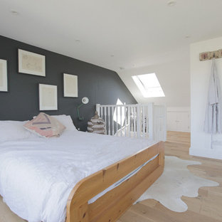 Photo of a medium sized contemporary master bedroom in London with grey walls, light hardwood flooring and beige floors.