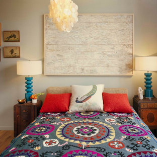 This is an example of an eclectic bedroom in New York with beige walls and medium hardwood floors.