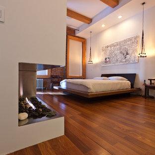 Esempio di una camera da letto design con pareti bianche e pavimento marrone