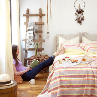 Example of an eclectic medium tone wood floor bedroom design in New York with white walls