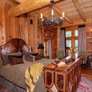 Imagen de dormitorio principal, rústico, de tamaño medio, con paredes marrones, suelo de madera en tonos medios, chimenea de esquina y marco de chimenea de ladrillo