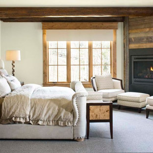 Large country master bedroom in Denver with white walls, carpet and a corner fireplace.