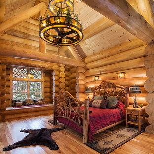 Mountain style master medium tone wood floor and yellow floor bedroom photo in New York with yellow walls