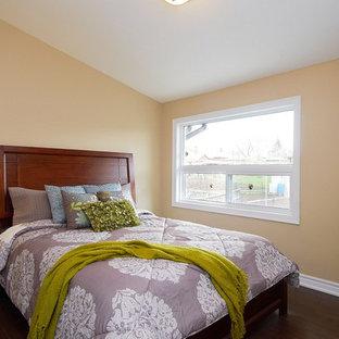 Trendy guest laminate floor bedroom photo in Toronto with beige walls