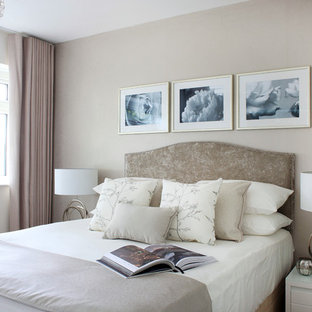Mid-sized transitional bedroom in London with beige walls.