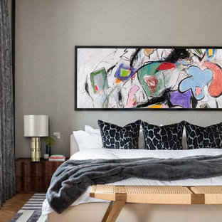 Inspiration for a contemporary master bedroom in London with grey walls, medium hardwood flooring and brown floors.