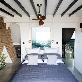 Ejemplo de dormitorio urbano, de tamaño medio, sin chimenea, con paredes blancas, suelo gris y marco de chimenea de ladrillo
