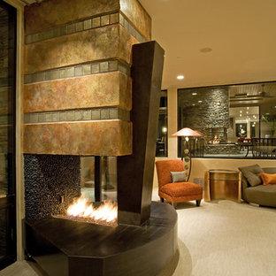 Diseño de dormitorio principal, clásico renovado, grande, con paredes beige, moqueta, chimenea de doble cara y marco de chimenea de metal