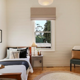 Design ideas for a transitional bedroom in Geelong with white walls, medium hardwood floors and brown floor.