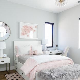 Modelo de habitación de invitados moderna, de tamaño medio, sin chimenea, con paredes grises, suelo de madera clara y suelo beige