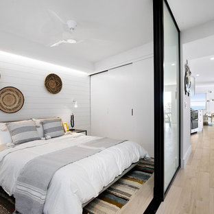Inspiration för ett litet maritimt sovrum, med vita väggar och beiget golv