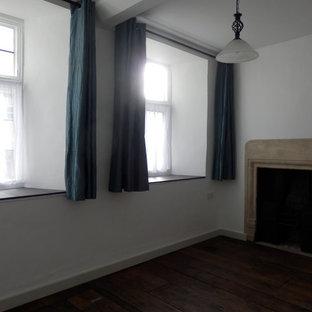 Modelo de habitación de invitados tradicional, de tamaño medio, con paredes blancas, suelo de madera oscura, estufa de leña, marco de chimenea de piedra y suelo marrón