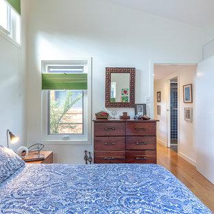 Foto de dormitorio principal, actual, pequeño, con paredes blancas, suelo de bambú y suelo marrón