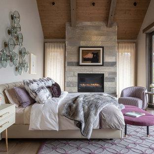 Ejemplo de dormitorio principal y madera, rural, con paredes blancas, suelo de madera clara, chimenea lineal y marco de chimenea de piedra