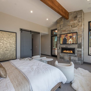 Diseño de dormitorio principal, rural, con paredes beige, moqueta, chimenea lineal, marco de chimenea de metal y suelo gris
