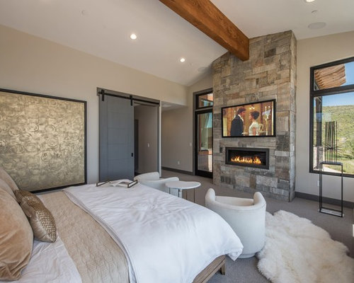 mountain style master carpeted and gray floor bedroom photo in salt lake city with beige walls - Modern Fireplace Design Ideas