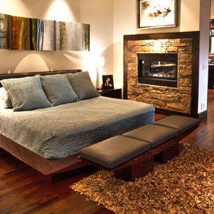 Ejemplo de dormitorio principal, minimalista, grande, con paredes beige, suelo de madera oscura, chimenea de doble cara y marco de chimenea de piedra
