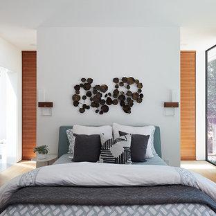 Immagine di una camera matrimoniale moderna con pareti bianche, parquet chiaro e nessun camino