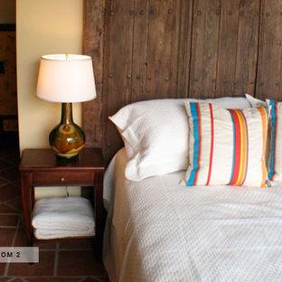 Diseño de habitación de invitados tropical, de tamaño medio, sin chimenea, con paredes beige, suelo de baldosas de terracota y suelo rojo