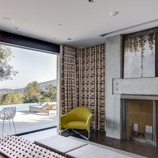 Ejemplo de dormitorio principal, minimalista, grande, con paredes blancas, suelo de piedra caliza, chimenea tradicional, marco de chimenea de hormigón y suelo marrón