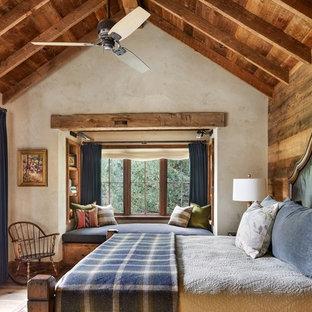 Immagine di una camera matrimoniale stile rurale con pareti beige, nessun camino e parquet chiaro