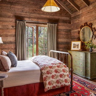 Rustic bedroom in Other with brown walls, no fireplace and medium hardwood flooring.