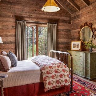 Modelo de dormitorio rural, sin chimenea, con paredes marrones y suelo de madera en tonos medios
