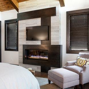 Diseño de dormitorio principal, actual, de tamaño medio, con paredes blancas, suelo de madera oscura, chimenea lineal y marco de chimenea de baldosas y/o azulejos
