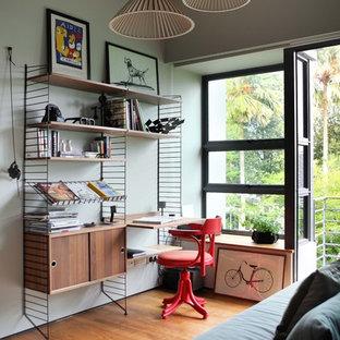 Foto de dormitorio actual con paredes verdes, suelo de madera en tonos medios y suelo marrón