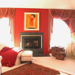 Immagine di una grande camera matrimoniale tradizionale con camino classico, pareti rosse, moquette, cornice del camino in pietra e pavimento beige